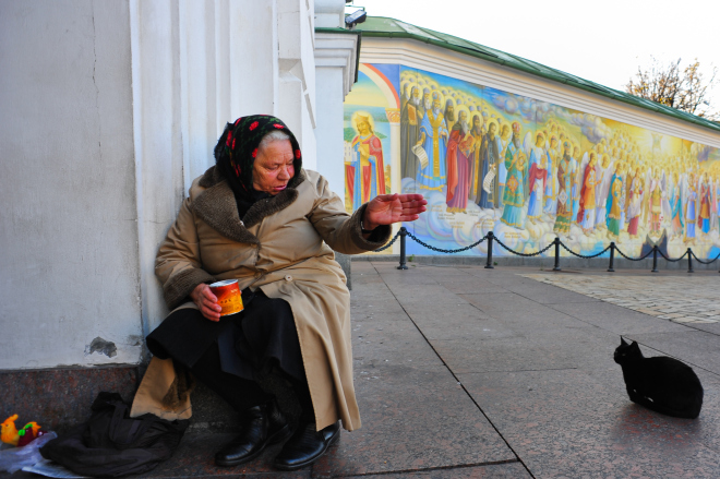 A beggar woman against the background of  Saint Sophia's Cathedral  fresco paintings. Kiev, Ukraine, Eastern Europe.