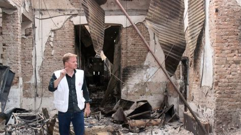 """In this Friday, Oct. 16, 2015 photo, Christopher Stokes, the general director of the medical charity, Doctors Without Borders, which is also known by its French abbreviation MSF, stands amid the charred remains of the organization's hospital, after it was hit by a U.S. airstrike in Kunduz, Afghanistan. Stokes says the """"extensive, quite precise destruction"""" of the bombing raid casts doubt on American military assertions that it was a mistake. (Najim Rahim via AP)"""